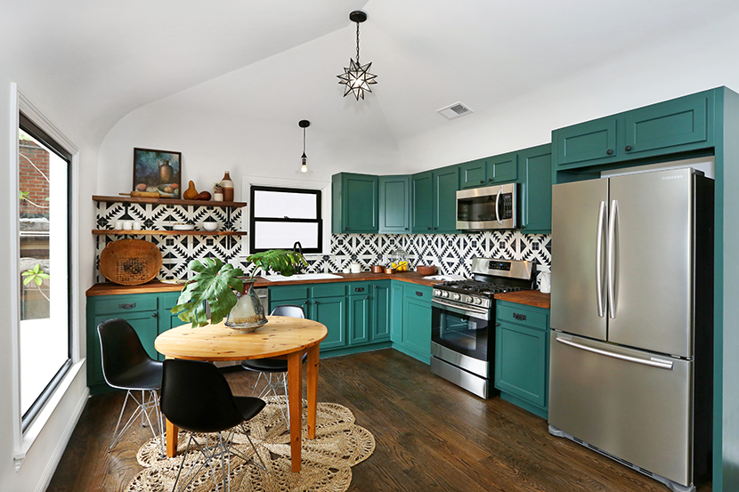 forrest gren painted cabinetry with butcher block countertops stainless steel appliances charming vintage details spanish southwestern style tile backsplash