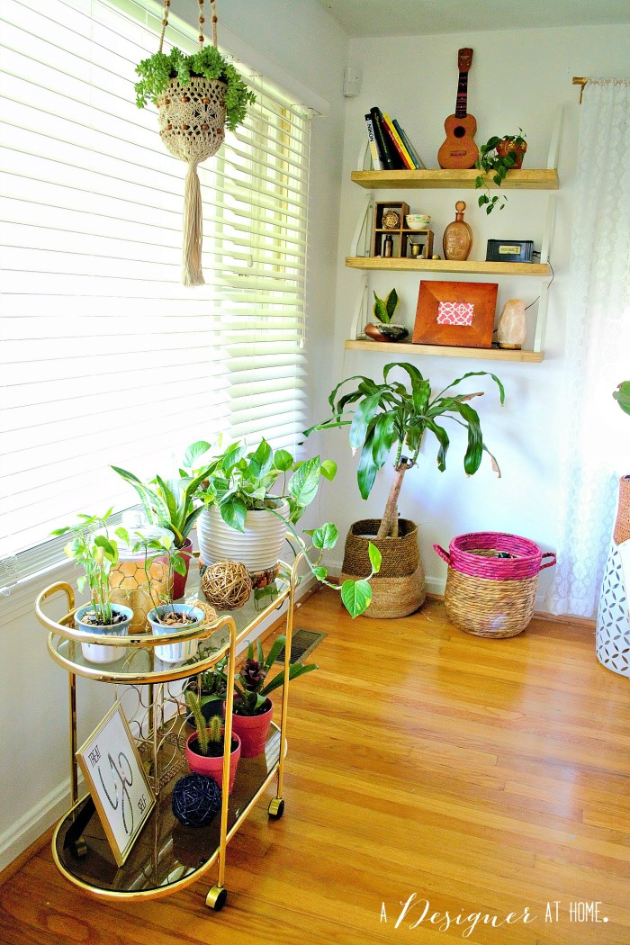the front window of the house is the perfect place for a bar cart turned plant stand and check out those shelves in the corner!