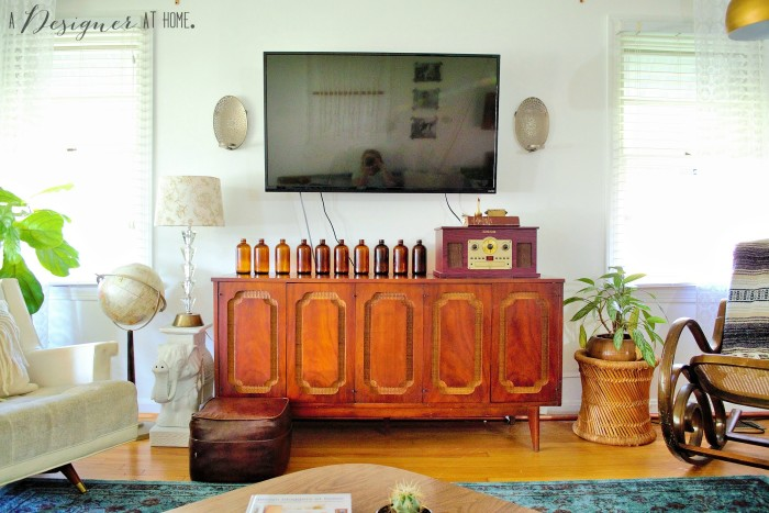 vintage credenza gone media console looks so good with all those rescued brown glass bottles!