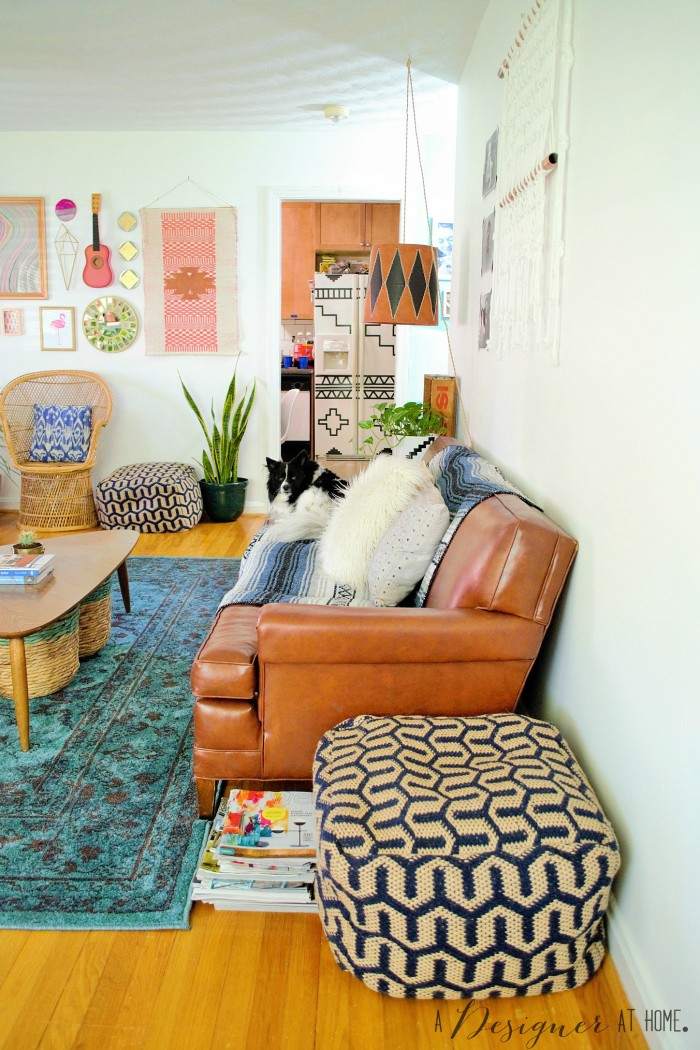 view from the front door included a really cool vinyl sofa and bright gallery wall a casually boho eclectic decorated space the living room of a 1950's brick ranch