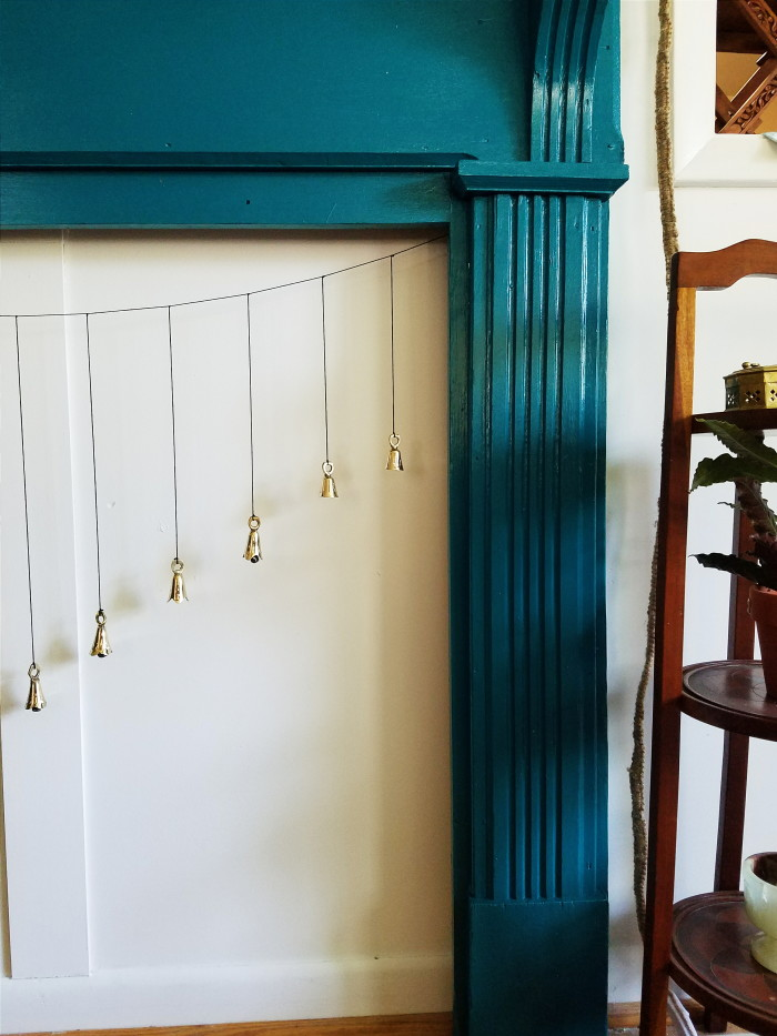 Teal fireplace with hanging bells for faux fireplace screen