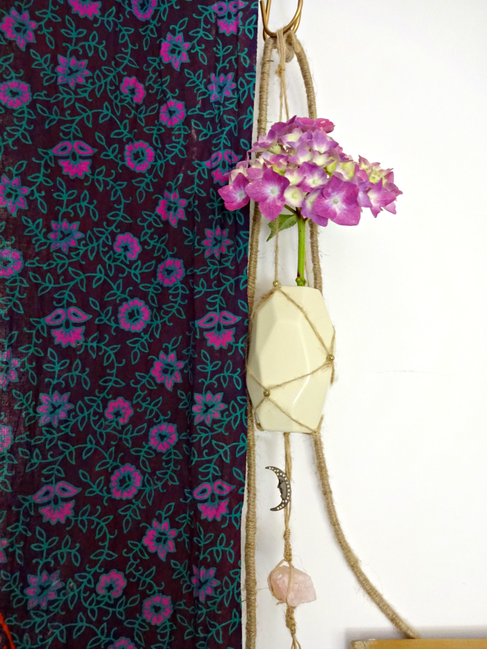 hydrangea in hanging handmade vase beside floral tapestry curtain
