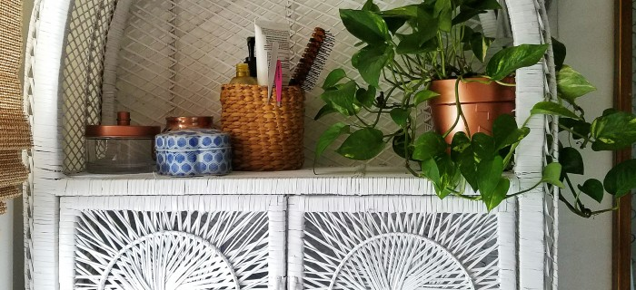 white painted wicker cabinet with baskets, thrifted containers to hide all of the bathroom essentials