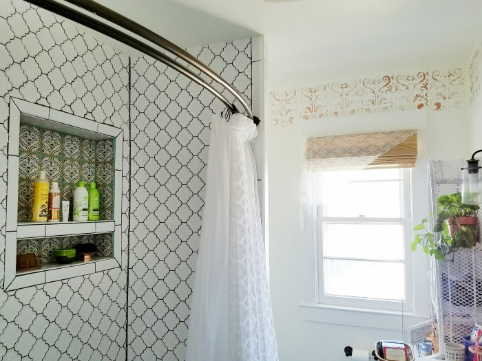 White tile with dark grout and lacey shower curtains