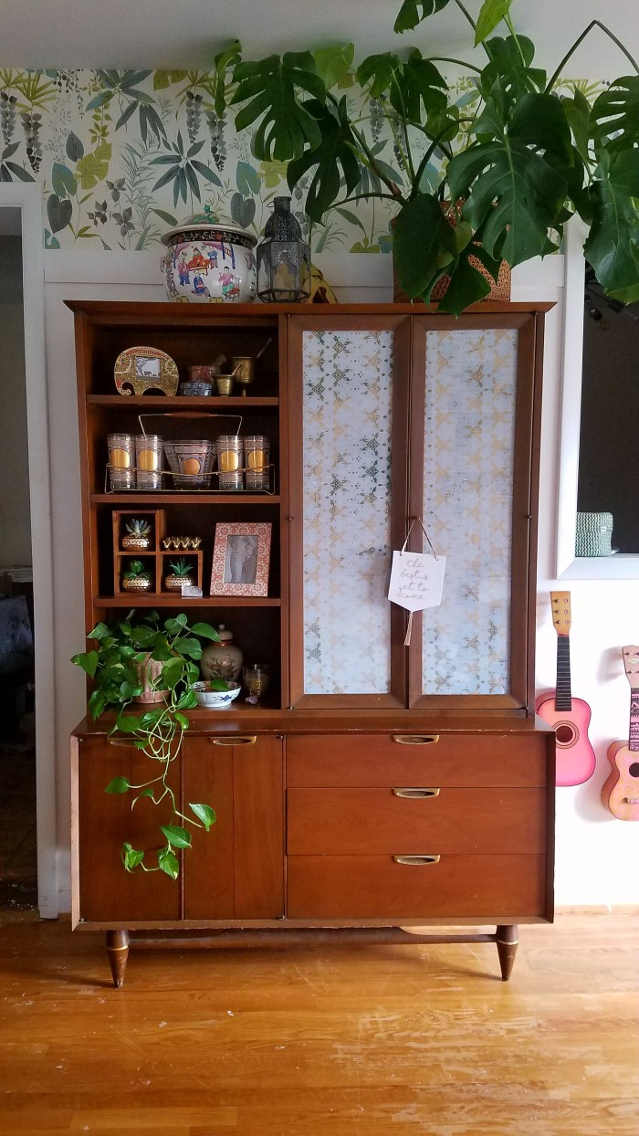 midcentury modern china cabinet with jungle boho wallpaper and lush plants