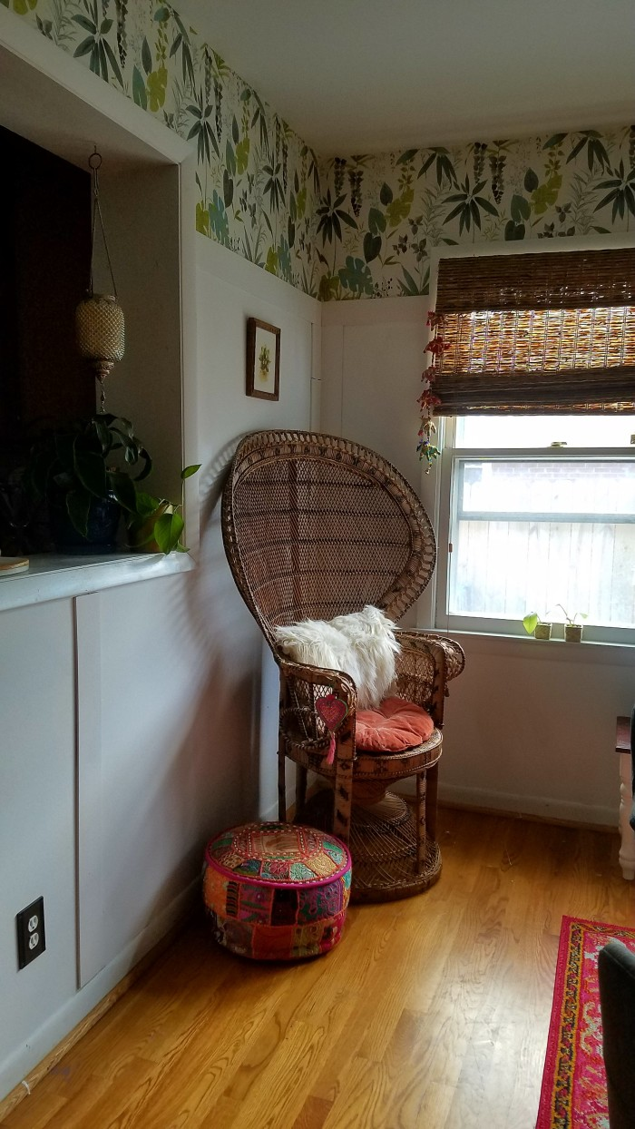 boho wicker chair from reading in the corner of the dining room | ethnic pink pouf and mongolian fur pillow