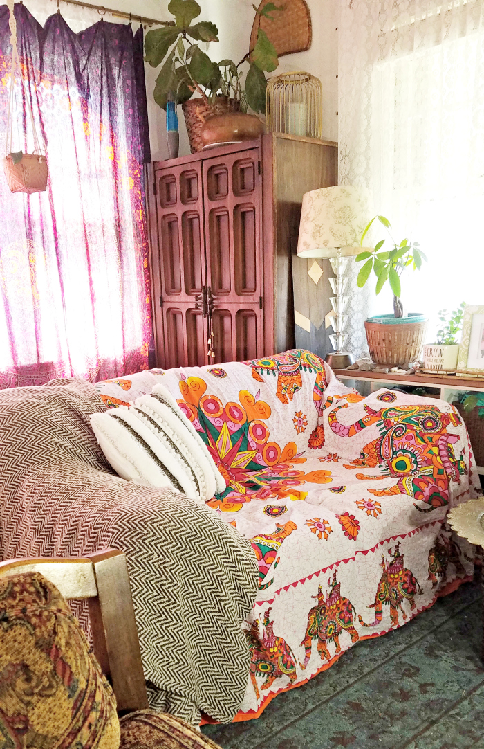 colorful boho elephant tapestry covered light denim wash of old hand me down sofa made cozy with a chevron cotton throw and a DIY handira inspired pillow